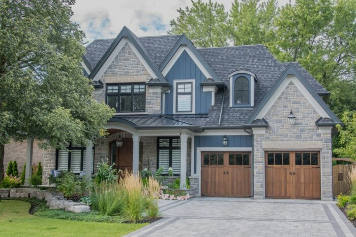 A large modern multi level residential executive home with brown and grey brick stone exterior, shingled roof, beautiful wooden garage doors, interlocked driveway, green gardens and lawn.