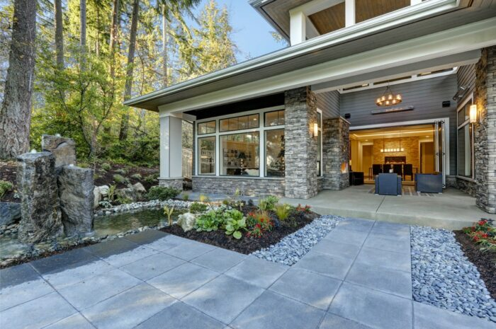 Luxurious new construction home exterior with front patio and perfect landscape design: nice garden pond with stone fountains. Northwest, USA